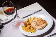 Lombo de carne de porco, prato lateral e vinho grelhados Imagens de Stock