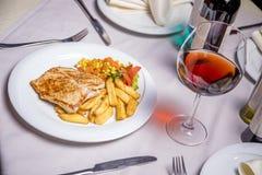 Lombo de carne de porco, prato lateral e vinho grelhados Fotografia de Stock