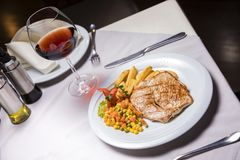 Lombo de carne de porco, prato lateral e vinho grelhados Fotos de Stock