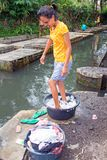 LOMBOK, INDONÉSIE - vêtements de lavage de jeune femme d'une manière démodée Photo libre de droits
