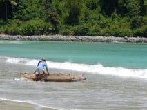 LOMBOK, INDONESIË - CIRCA 2014: Een visser neemt zijn boot in het overzees op het Eiland Lombok in Indonesië royalty-vrije stock afbeelding