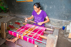 LOMBOK, INDONESIA - DECEMBER 30, 2016: Woman weaving on a loom in Indonesia Stock Photos