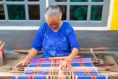 LOMBOK, INDONESIA - 30 DICEMBRE 2016: Tessitura della donna su un telaio i Fotografia Stock Libera da Diritti