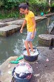 LOMBOK, INDONESIA - il lavaggio della giovane donna copre di un modo antiquato Fotografia Stock Libera da Diritti