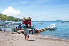 Women workers transporting suitcases from the boats in the harbor from Bangsal on Lombok in Indonesia Stock Photography