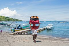Women workers transporting suitcases from the boats in the harbor from Bangsal on Lombok in Indonesia Stock Photos