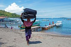 Women workers transporting suitcases from the boats in the harbor from Bangsal on Lombok in Indonesia Stock Photo