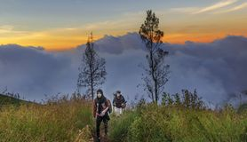 Lombok, Indonesia June 2015: Hikers walking along hiking trails at sunset to reach Mt Rinjani volcanic crater before it gets dark Stock Photography