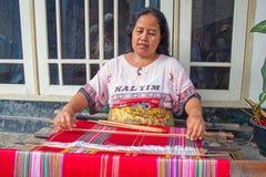 LOMBOK, INDONESIEN - 30. DEZEMBER 2016: Frau, die auf einem Webstuhl I spinnt Stockbild