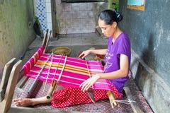 LOMBOK, INDONESIEN - 30. DEZEMBER 2016: Frau, die auf einem Webstuhl spinnt Stockfotografie