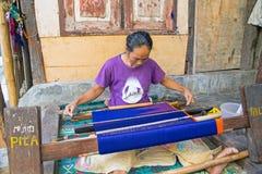 LOMBOK, INDONESIEN - 30. DEZEMBER 2016: Frau, die auf einem Webstuhl spinnt Lizenzfreie Stockfotos