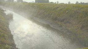 Mist rising from an irrigation ditch in a natural park during autumn. Lomellina is a historic region located in Lombardy, famous for its castles, farmhouses stock footage
