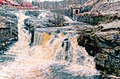 Lomma river rushing waterfall. Colorful water containing iron compounds. HDR view. Norwegian winter. Baerum village in Akershus Norway Royalty Free Stock Image