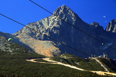 Lomnicky peak and ski slope in a sunny autumn day, High Tatras. Lomnicky peak and Lomnicky saddle in a sunny autumn day with ski slopes without snow, cable cars Royalty Free Stock Photo