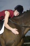 Lomo de caballo femenino Rider Hugging Horse fotos de archivo