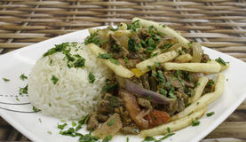 Lomo Saltado. A peruvian dish made with sautéed beef, tomatoes, onion, fried potatoes and rice Stock Photography