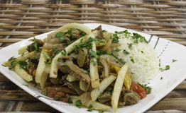 Lomo Saltado. A peruvian dish made with sautéed beef, tomatoes, onion, fried potatoes and rice Stock Photos