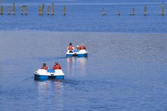 Lomond pedalo. Two sets of daytrippers in pedalos on Loch Lomond, Scotland royalty free stock photography