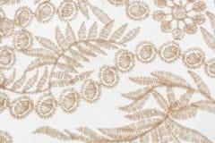 Lona de encaje beige con adornos de la planta en el fondo blanco Foto de archivo