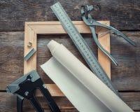Lona do artista no rolo, na barra de madeira da maca, nos alicates da lona, na arma do grampo e na régua imagens de stock