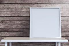 Lona en blanco del marco en el escritorio en sitio del desván con acortar el PA Imágenes de archivo libres de regalías