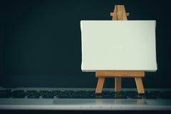 Lona en blanco y caballete de madera en el ordenador portátil Imagen de archivo libre de regalías