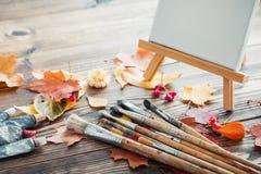 Lona en el caballete, los tubos de la pintura, los cepillos y las hojas de otoño en el escritorio Fotos de archivo