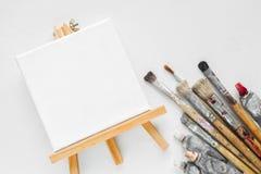 Lona en el caballete, los tubos de la pintura y el paquete de cepillos para pintar Imagen de archivo libre de regalías