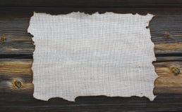 Lona quemada en un fondo de madera Imagen de archivo