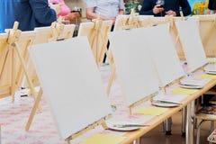 Lonas, escovas, paletas na tabela pronta para os masterclass do estúdio da arte Fotos de Stock
