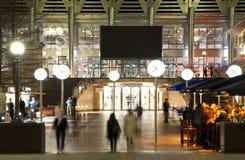 LONDEN, CANARY WHARF het UK - 4 APRIL, de vierkante mening van Canary Wharf van 2014 in nachtlichten met beambten die uit koelen Stock Afbeeldingen