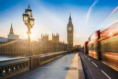 Londen, Engeland - iconisch Big Ben en de Huizen van het Parlement met lamp posten en bewegende beroemde rode dubbeldekkerbussen royalty-vrije stock foto