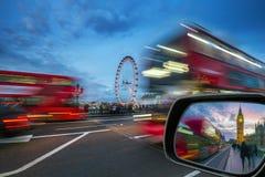 Londen, Engeland - iconische rode dubbeldekkerbussen in beweging op de Brug van Westminster met Big Ben en Huizen van het Parleme Royalty-vrije Stock Fotografie