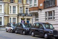Londen, Groot-Brittanni? 12 april, 2019 Kensingtonstraat Cabineparkeren De cabine van Londen wordt beschouwd als de beste taxi in stock foto's