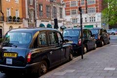 LONDEN, het UK - 14 April, 2015: drie uitstekende cabines die van Londen in de straat wachten Stock Afbeeldingen