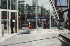 LONDEN, het UK - 14 April, 2015: jonge bedrijfsvrouw langs de weg met verkeer lopen en rode bussen die op achtergrond Stock Foto