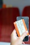 Londen, het UK - 31 Augustus 2016: De hand van de vrouw houdt een treinkaartje en een smartphone Stock Foto
