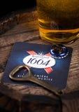 LONDEN, HET UK - 10 AUGUSTUS, 2018: Kronenbourg 1661 bieronderlegger voor glazen met flessenbovenkant en opener en glas bier bove Royalty-vrije Stock Fotografie