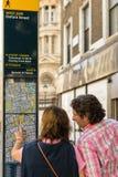 Londen, het UK - 30 Augustus 2016: Twee niet geïdentificeerde toeristen controleren de straatkaart in het Westeneind Royalty-vrije Stock Afbeelding