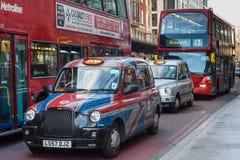 Londen, het UK - circa Maart 2012: Dubbele dekbussen en auto's met Britse vlag op de straten van Londen Royalty-vrije Stock Fotografie