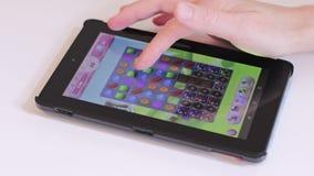 Londen/het UK - 9 Juli 2019 - Vingers die het spel van de Suikergoedverbrijzeling op een Kindle Fire-tablet spelen stock footage
