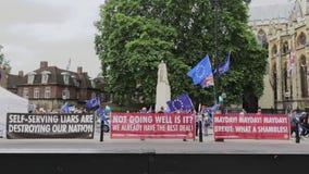 Londen/het UK - 26 Juni 2019 - banners de pro-EU en protesteerders met Europese Unie vlaggen tegenover het Parlement in Westminst stock videobeelden