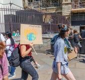 Londen/het UK - 26 Juni 2019 - Jonge vrouwen houdt een klimaatveranderingteken buiten het Parlement in Westminster stock fotografie
