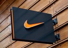 LONDEN, HET UK - 02 JUNI, 2017: Nike-embleem op zwarte vertoningsplaat op houten achtergrond Nike, N.v. is een Amerikaans bedrijf Royalty-vrije Stock Foto's
