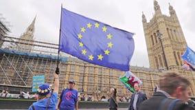 Londen/het UK - 26 Juni 2019 - protesteerders de pro-EU die anti-Brexit Europese Unie en van Wales vlaggen buiten het Parlement i stock videobeelden