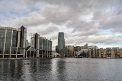 Londen, het UK - 05 Maart, 2019: De vlakten en de huizen langs de banken van Canary Wharf, houden toezicht rivier op zijflats stock fotografie