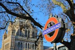 LONDEN, HET UK - 28 NOVEMBER, 2016: Het Ondergrondse teken van Londen met duiven en het Biologiemuseum op de achtergrond in Zuide stock afbeelding