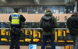 LONDEN, het UK - 17 Oktober, 2017: de Britse lettende op Reizigers die van de vervoerpolitieman op het informatievertrek letten stock afbeeldingen