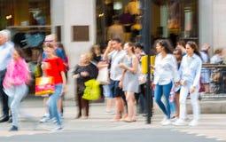 Londen, het UK Veel lopende mensen, toerist en Londoners, die de Piccadilly-circusverbinding kruisen royalty-vrije stock foto