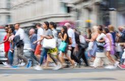 Londen, het UK Veel lopende mensen, toerist en Londoners, die de Piccadilly-circusverbinding kruisen stock fotografie